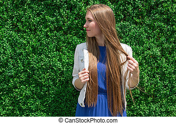 Young girl on green background of leaves