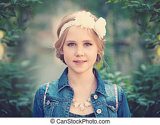 Young Girl on Green Foliage Background Outdoors