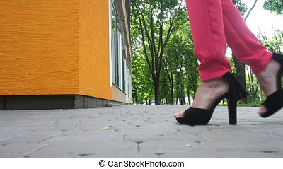 young girl on high heels black walking down the street