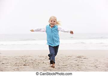 Young Girl On Holiday Running Along Winter Beach