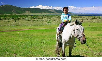 Young girl on horseback in Mongolian landscape