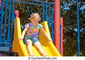 young girl on playground slide
