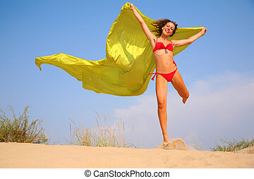 Young girl on sand with yellow fabric shawl in hands