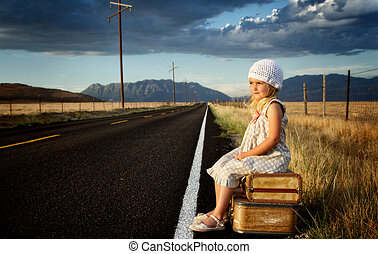 Young girl on side of road with suitcases - Young girl on...