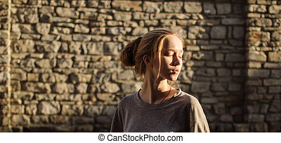 Young girl on the background of an old stone wall at sunset.