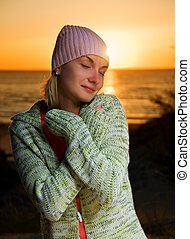 Young girl on the beach at sunset time