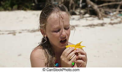Young girl on the beach eating mango fruit