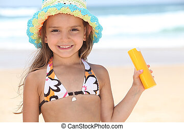 Young girl on the beach holding suncream
