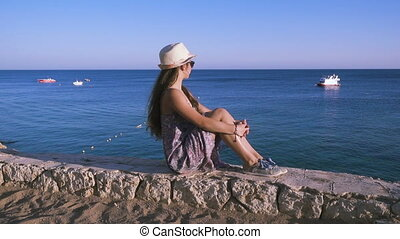 girl on the coast looking to azure sea - Young girl on the...