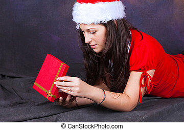 young girl on the floor in red with christmas clothes looking in the gift box