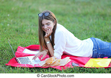 young girl on the nature of eating fast food and working at a laptop
