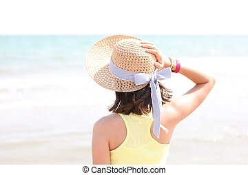 young girl on the seashore with straw hat and light tones