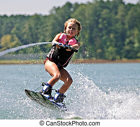 Young Girl on Wakeboard - A young girl jumping waves on her...