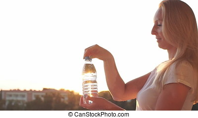 Young girl opens a bottle of water at sunset. Slow motion