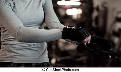 Young girl or woman putting on gloves in gym. - Young girl...