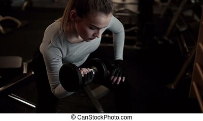 Young girl or woman with dumbbells, doing workout in a gym....