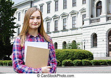 Young girl outdoor holding books