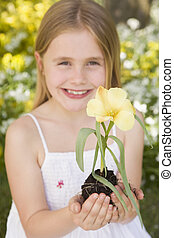 Young girl outdoors holding flower smiling