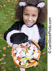 Young girl outdoors in cat costume on Halloween holding...