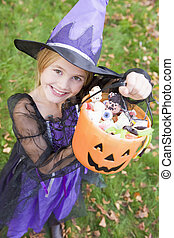Young girl outdoors in witch costume on Halloween holding...