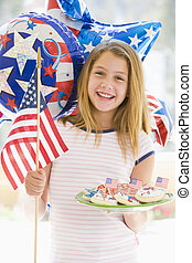 Young girl outdoors on fourth of July with flag and cookies smil