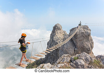 Young girl over abyss - Young woman crossing the chasm on...
