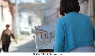 Young girl painter painting a cityscape with watercolor