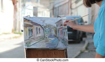 Young girl painter painting old street with watercolor