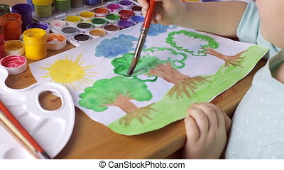 Young girl painting a brown trees with green leaves on white paper