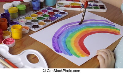 Young girl painting a colored rainbow on white paper