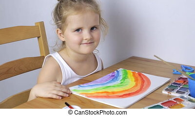 Young girl painting a picture at home