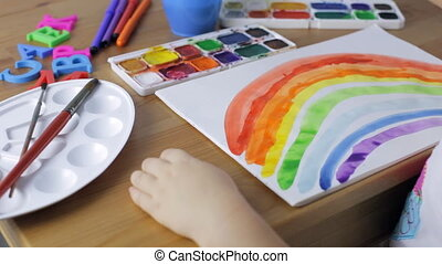 Young girl painting a rainbow at home