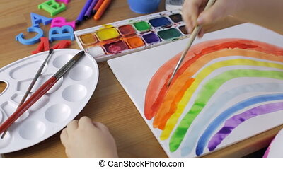 Young girl painting a rainbow. Watercolor painting concept