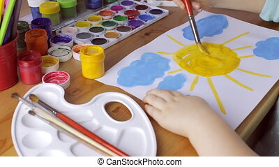 Young girl painting a yellow sun on white paper