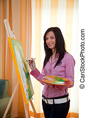 Young girl painting on an easel