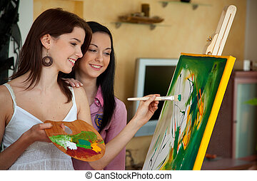 Young girl painting on an easel - Young woman paints in her ...
