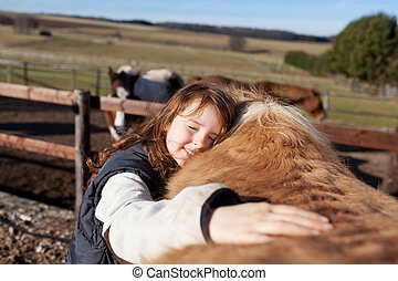 Young girl petting her horse - Young girl petting her ...