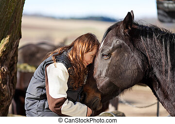 Young girl petting her horse - Young girl sitting in the ...