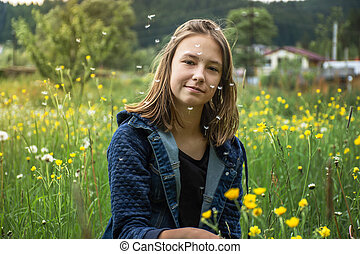young girl picks flowers in a summer meadow