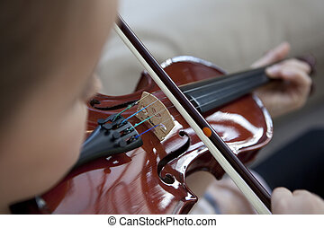 Young girl playing a violin with selective focus on the bow and bridge of the instrument.