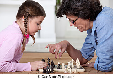 Young girl playing chess with grandma