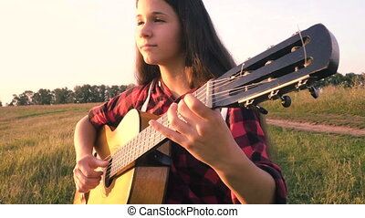 Young girl playing guitar on meadow at the sunset, slow...