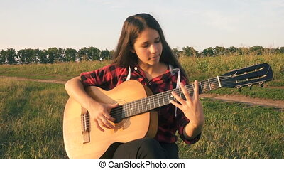 Young girl playing guitar on meadow at the sunset - Young...