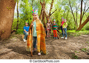 Young girl playing Red Indian chief in the forest