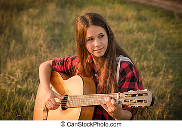Young girl playing the guitar on meadow at sunset