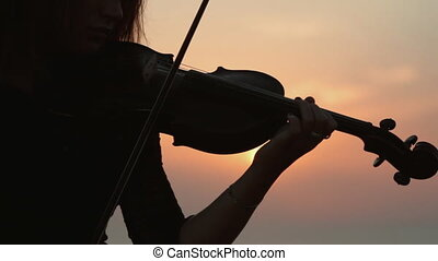 Young girl playing the violin at the background of amazingly beautiful sunset on the sea