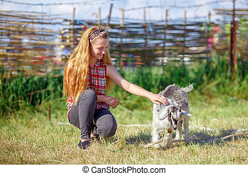 young girl playing with a small baby goat