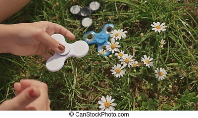 Young girl playing with a white spinner on the lawn on a...
