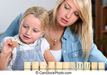 Young girl playing with dominoes