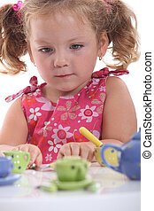 Young girl playing with her tea set